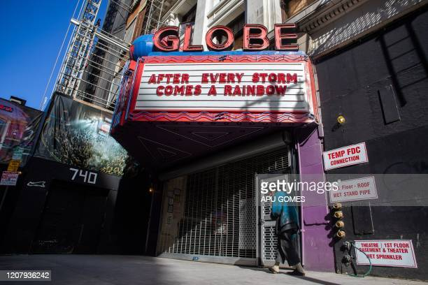TOPSHOT A homeless man walks by a closed theater in Downtown Los Angeles on March 21 during the novel coronavirus outbreak All 40 million residents...