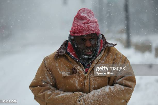 A homeless man walks through the streets of Boston as snow falls from a massive winter storm on January 4 2018 in Boston United States Schools and...