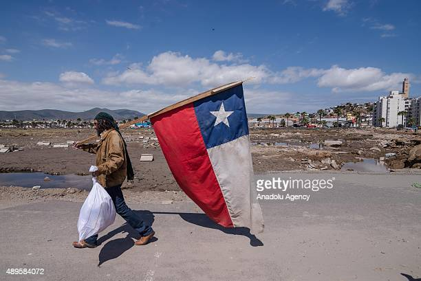 A homeless man walks with national flag as local residents clean their home of the debris left by the tsunami that ensued an 83 quake that left 12...