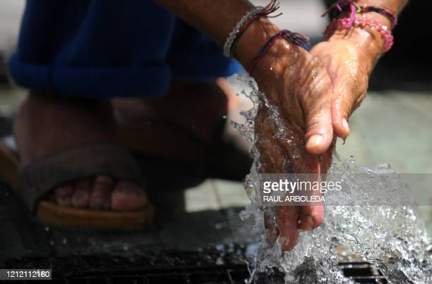 A homeless man washes his hands in a fountain in Medellin Antioquia Department Colombia on March 22 on World Water Day The UN's food agency marked...
