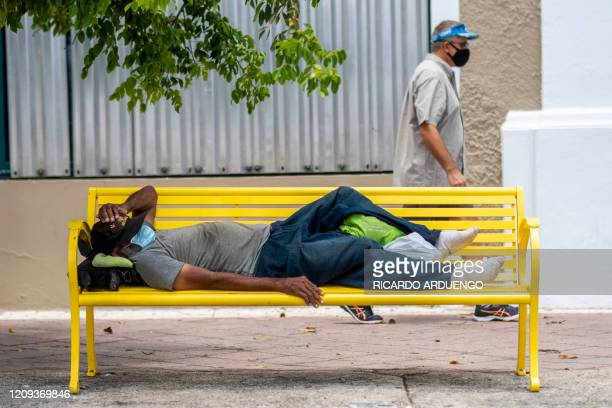 A homeless man wearing a protective mask lays on a bench as a man walks by in Old San Juan Puerto Rico on April 7 2020 On March 15 Puerto Rico...