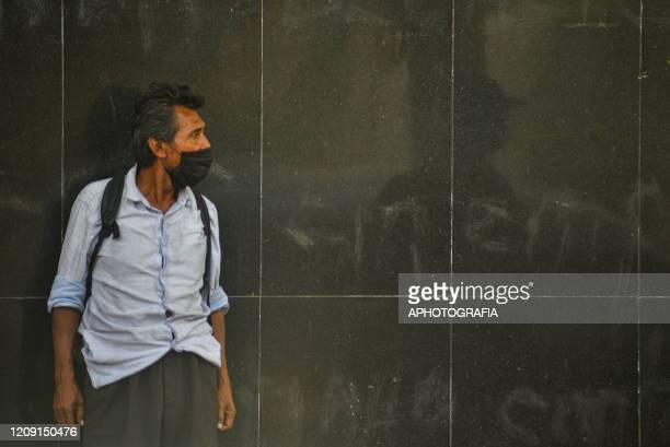 A homeless man wearing a protective mask observes as people pass by on April 2 2020 in San Salvador El Salvador On March 21st President Nayib Bukele...