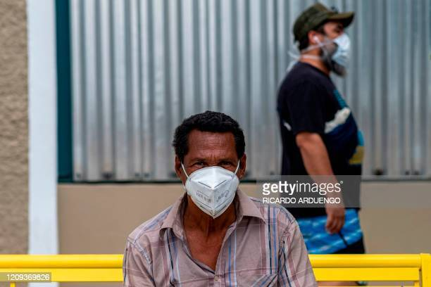 A homeless man wearing a protective mask sits on a bench as a man walks by in Old San Juan Puerto Rico on April 7 2020 On March 15 Puerto Rico...