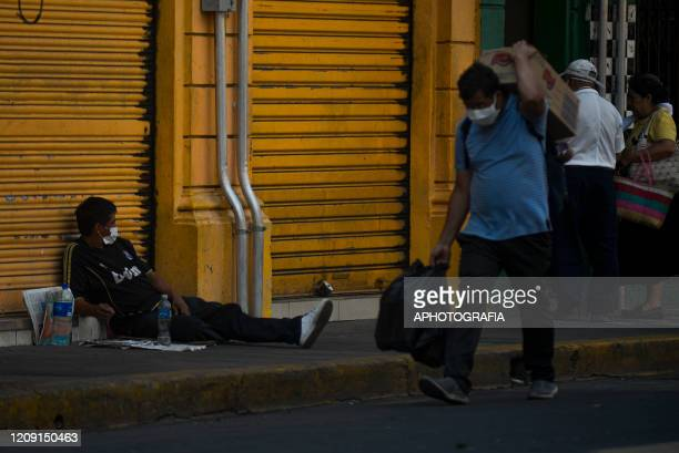 A homeless man wearing a protective mask watches people pass by on April 2 2020 in San Salvador El Salvador On March 21st President Nayib Bukele...