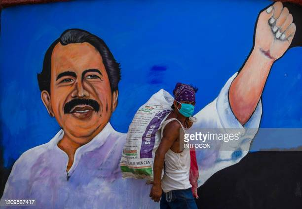 Homeless man wears a face mask against the spread of the new coronavirus, COVID-19, as he walks past a mural depicting Nicaraguan President Daniel...