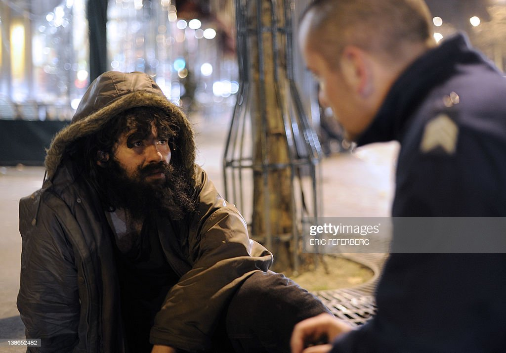 A homeless man who lies on the pavement in the center of Paris talks with a policeman working for the BAPSA service witch help homeless people. The temperatures dropted to -7° on February 09, 2012 in the French capital .