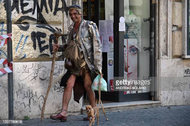 A homeless man with a dog leaves after receiving a bag of food from volunteers from the association Circolo San Pietro economic cuisine and...