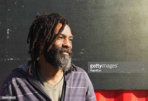 homeless man with dreadlocks and beard smiles wistfully - homeless person stock pictures, royalty-free photos & images