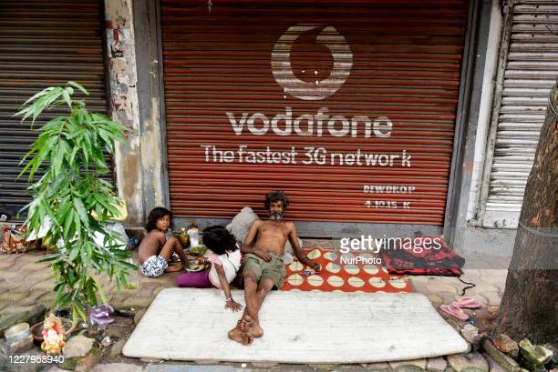 Homeless man with his children sit in front of a Vodafone store during a lockdown imposed by the state government against the surge in COVID-19...