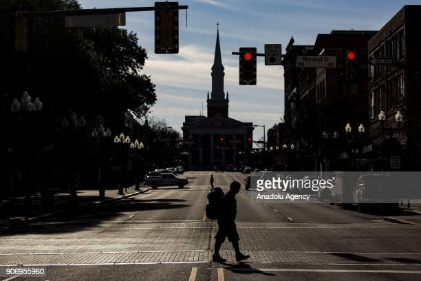 Homeless man with his pack and sleeping rolls crosses a street in Shreveport, Louisiana, United States on January 04, 2018.