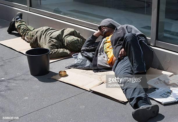 Homeless men asleep on the sidewalk in New York City