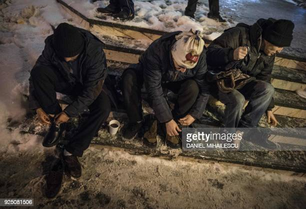 Homeless men exchange their shoes with new ones received from the Social Service of City Hall next to The North Railway Station in Bucharest on...