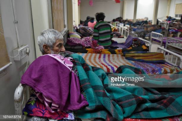 Homeless men lie on their beds inside a shelter home at Sarai Kale Khan on December 18 2018 in New Delhi India There are some 83 permanent shelters...