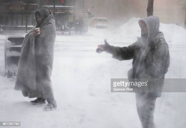 Homeless men pause outside of a coffee shop on the streets of Boston as snow falls from a massive winter storm on January 4 2018 in Boston United...