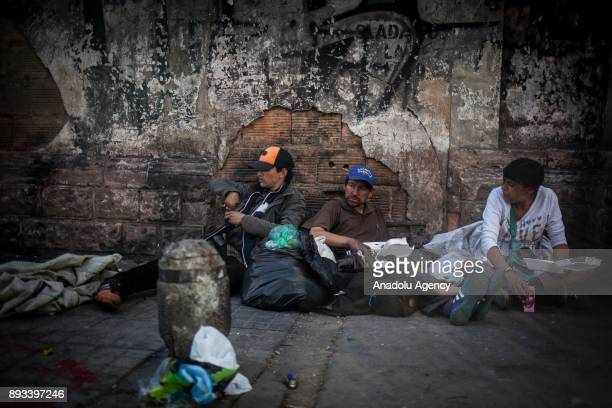 Homeless men sit on the ground with their foods distributed by volunteers in Bogota Colombia on December 15 2017 Homeless people eat their meal...