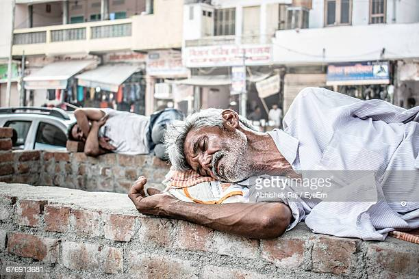 homeless men sleeping on brick walls - unemployment stock photos and pictures
