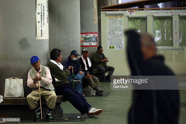 Homeless men wait around in the slum area of Kamagasaki on April 23 2016 in Osaka Japan Kamagasaki a district in Japan's second largest city Osaka is...
