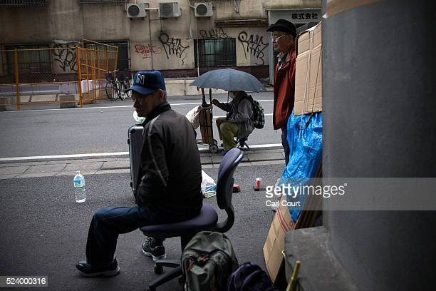 Homeless men wait in the street for the offer of work in the slum area of Kamagasaki on April 23 2016 in Osaka Japan Kamagasaki a district in Japan's...