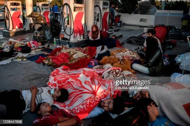 Homeless migrants and refugees sleep at a gas station after a fire destroyed Greece's largest Moria refugee camp on the island of Lesbos, early on...
