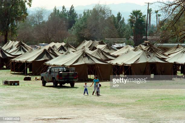 A homeless mother and her children walk near a tent city at Winnetka Recreation Center on January 22 1994 as California National Guard ste up the...