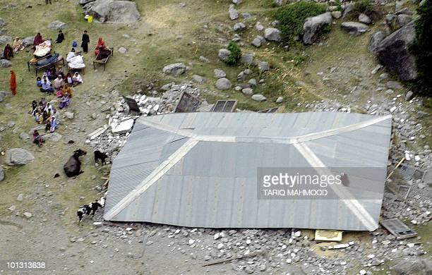 Homeless Pakistani people sit beside their collapsed house following a massive earthquake in Balakot town some 300 kilometers from Peshawar 08...