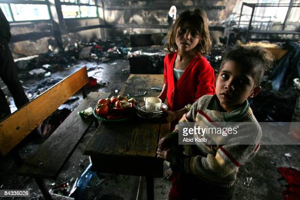 Homeless Palestinian children stand in a burnt classroom at a United Nations school after it was hit by Israeli shelling on January 17 2009 in Beit...