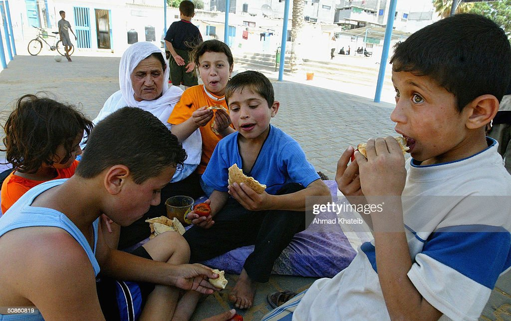 A homeless Palestinian family eats whilst staying temporarily at a United Nations school after their house was recently demolished during an Israeli army raid May 20, 2004 in Rafah, Gaza. Israeli troops and tanks pushed further into the besieged Rafah refugee camp on Thursday despite international outrage at the killing of 40 Palestinians in the bloodiest Gaza raid in years.
