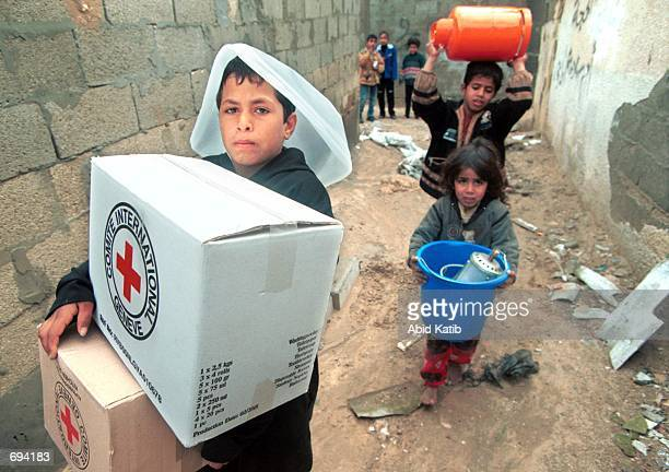 Homeless Palestinians children carry hygiene kits cooking sets gas lamps and cookers which were given to their family and other families by the...