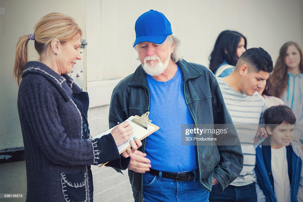 Homeless people and families in need signing up for assistance : Stock Photo