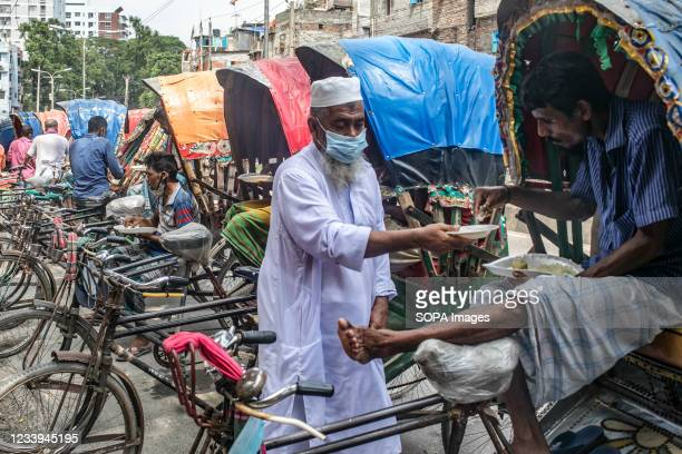 """Homeless people and Rickshaw-pullers seen receiving food donated by """"Showkat Tehari Ghar food distribution"""" during the national wide Covid-19..."""