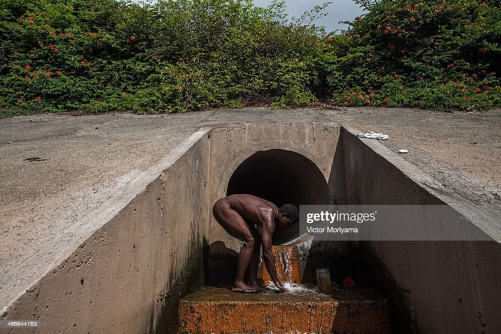 Drought forces sao paulo to consider water rationing photos and a homeless people bathes in sewage pipe that flows into the tiete river the largest sciox Images