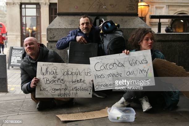 """Homeless people hold signs reading """"What about us Boris - were we gunna isolate? Help!"""", and """"Corona Virus has made all my donations disapear"""" as..."""