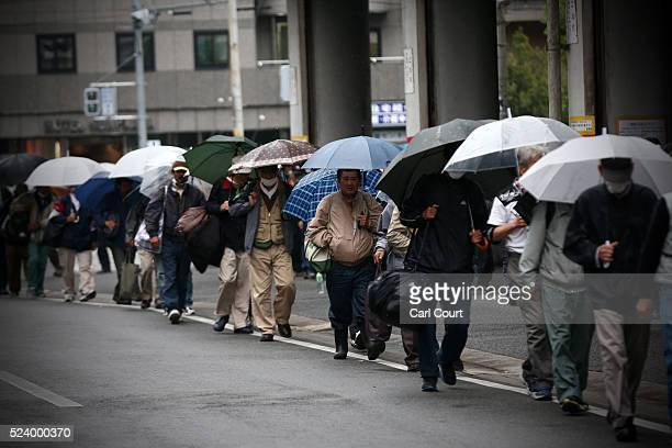 Homeless people queue to access a shelter in the slum area of Kamagasaki on April 23 2016 in Osaka Japan Kamagasaki a district in Japan's second...