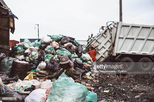 Homeless People Searching In Garbage Heap