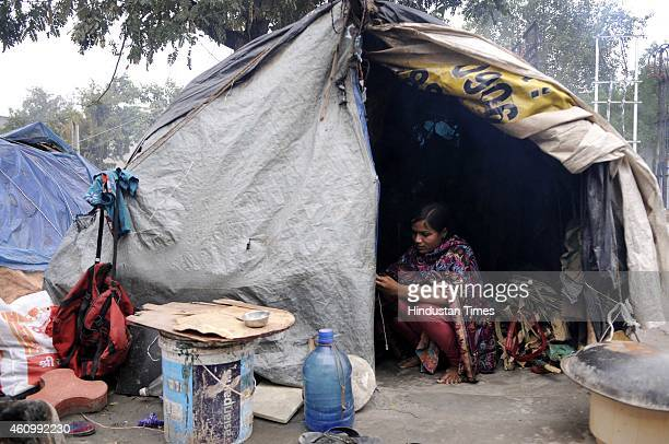 Homeless people sit by their roadside shanty during a cold and foggy day on January 3 2015 in Noida India Delhi NCR has a homeless population of more...