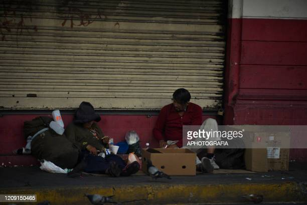 Homeless people sit on the street where they live through the COVID19 crisis on April 2 2020 in San Salvador El Salvador On March 21st President...