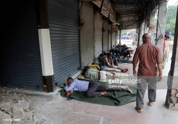 Homeless people sleep in front of closed shops at Chandani Chowk main market during the lockdown in Old Delhi. Chandani Chowk is busy shopping market...