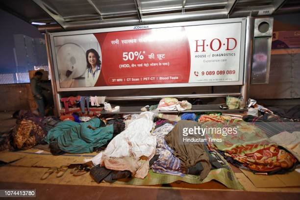 Homeless people sleep on a road pavement outside AIIMS on December 18 2018 in New Delhi India There are some 83 permanent shelters and 115 Porta...