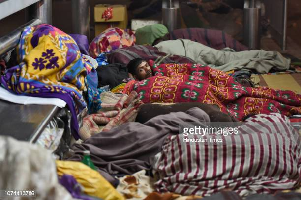 Homeless people sleeping on a road pavement outside AIIMS on December 18 2018 in New Delhi India There are some 83 permanent shelters and 115 Porta...