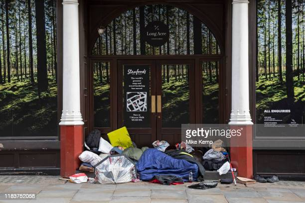 Homeless people sleeping rough in a doorway surrounded by an idillic picture of a natural forest landscape in Covent Garden in London England United...
