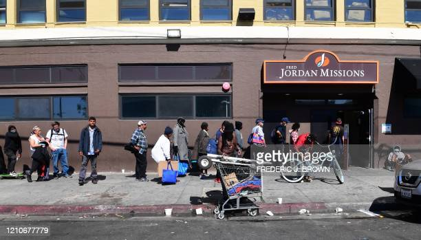 Homeless people wait in line for a morning meal at the Fred Jordan Missions Los Angeles, California on April 22 amid the novel coronavirus pandemic....