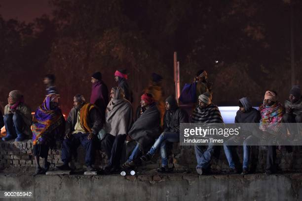 Homeless people watching a movie in a temporary open air theatre on the eve of New Year near Nigambodh Ghat on December 31 2017 in New Delhi India