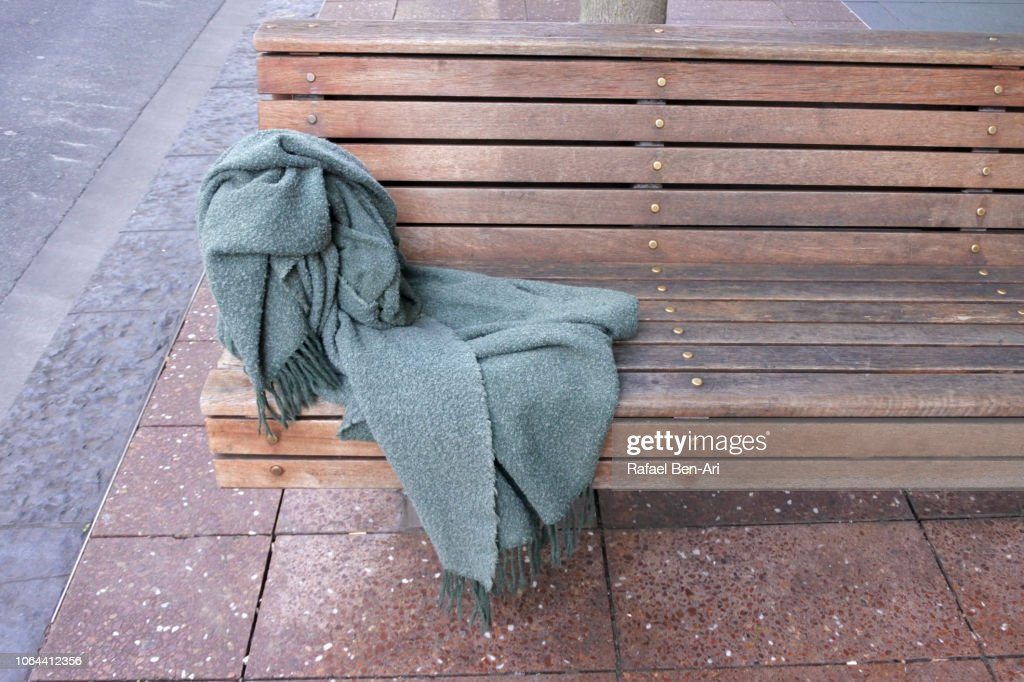 Homeless Person Blanket on a street  Bench : Stock Photo