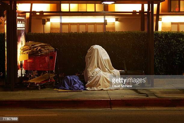A homeless person covers up on a bus stop bench before dawn October 12 2007 in downtown Los Angeles California Los Angeles city officials recently...