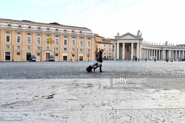 A homeless person crosses the Vatican's empty St Peter's Square on April 6 after almost a month of the Vatican's closure to tourists as part of a...