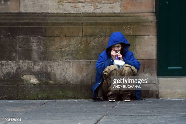 TOPSHOT A homeless person crouches beside a wall in a Glasgow city centre street on March 27 2020 Britain is under lockdown its population joining...