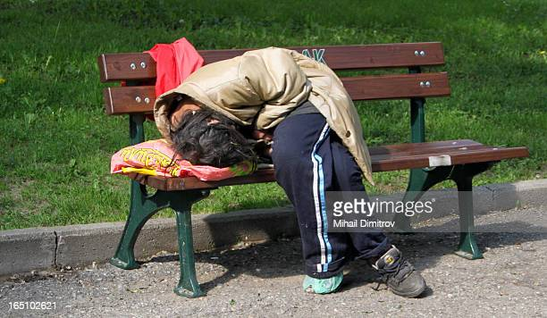 Homeless person fells asleep on a park bench under the warm may sunlight in Sofia, Bulgaria in the downtown area near the Parlament of Bulgaria.