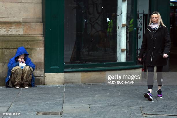 TOPSHOT A homeless person glances up as a woman passes by on a Glasgow city centre street on March 27 2020 Britain was under lockdown its population...