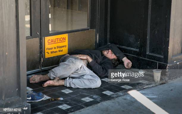 Homeless person is passed out in front of a business in Westwood Village on August 7, 2018 in Los Angeles, California. Millions of tourists flock to...