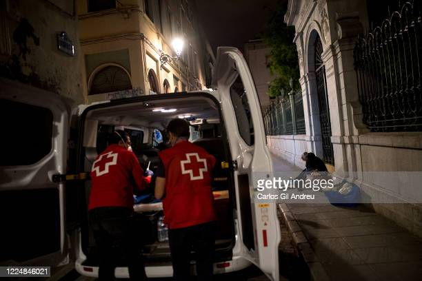 A homeless person is seen on the street as Red Cross volunteers prepare an aid pack for him on May 13 2020 in Granada Spain Since the start of the...